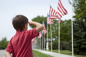 Young boy salutes flags of Memorial Day display
